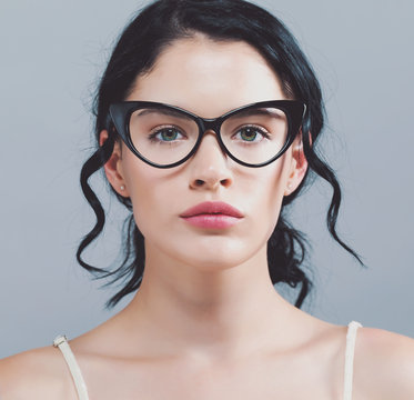Young woman with eye glasses on a gray background