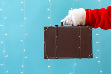 Santa holding a suitcase on a shiny light blue background