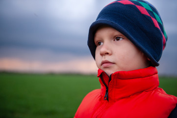 Romantic boy in red jacket is standing on green field sown with winter wheat against backdrop of rainy clouds and dreams. Child spends summer holidays in village. Experience pre-school education.