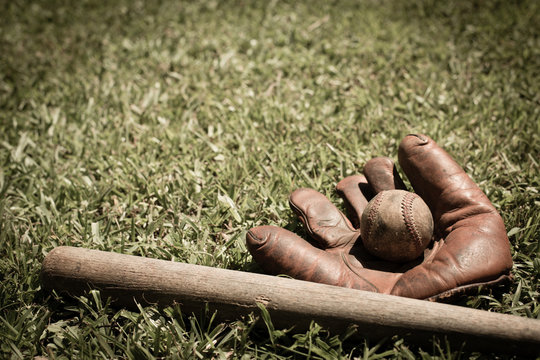 Old, Well-Used Baseball, Glove and Bat in Grass, Room for Text