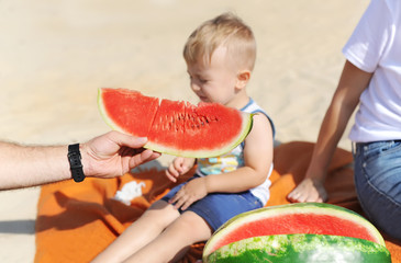 Family is eating a watermelon together on the sandy beach.