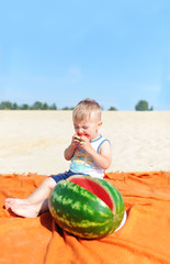 Baby boy eating watermelon slice against beach background