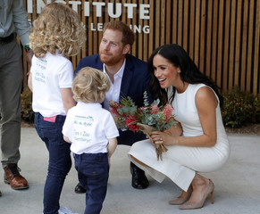 Britain's Prince Harry and Meghan, Duchess of Sussex receive native flowers from Finley Blue and Dasha Gallagher, left, at Taronga Zoo in Sydney