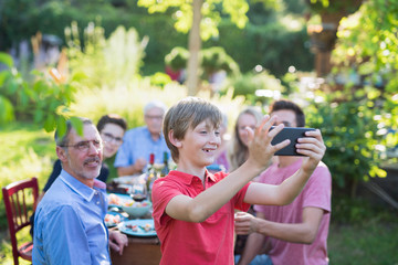 during a bbq a young boy does a selfie with the whole family