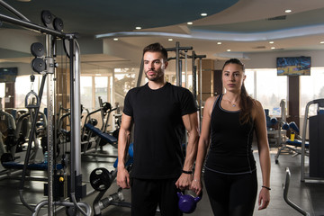 Young Couple Posing In The Gym with Kettle-Bell