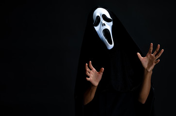 The boy in black cover with white ghost mask cosplay to devil acting performing clamber frightening gost on black background, concept for halloween fashion festival