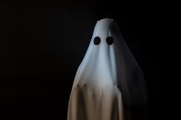Someone covered with white cloth with big black eyes on black background look like ghost in night. Concept for funny playing in halloween festival