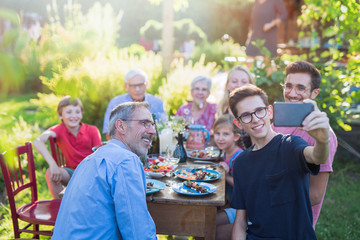 during a bbq a boy does a selfie with the whole family