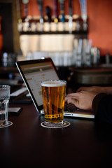 Brews and Business. a man works with technolgy as he enjoys a cold beer in a bar