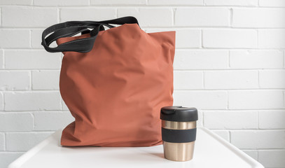 Resuable coffee cup and shopping tote bag on white table against brick wall