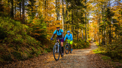 Cycling, mountain biker couple on cycle trail in autumn forest. Mountain biking in autumn landscape forest. Man and woman cycling MTB flow uphill trail. Fototapete
