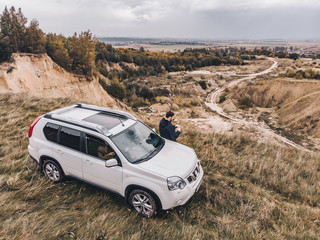 white suv at the top of the hill in autumn overcast weather. man standing near car around wild nature