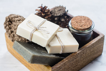 Spa, beauty skincare body concept. Handmade soap, coffee body scrub and body brush in wooden box on white marble background. Closeup