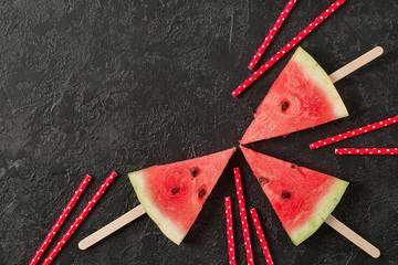 Fresh watermelon cut into pieces on dark background