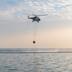 A fire helicopter collects water into the sea and flies toward the mountains to extinguish a forest fire. Rescue operation. Forest Fire Prevention