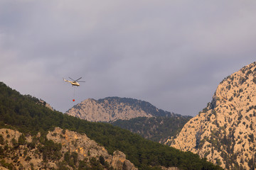 A fire helicopter with a full basket of water flies to extinguish a forest fire against the backdrop of mountains, painted in bright orange sun color. Rescue operation. Forest Fire Prevention