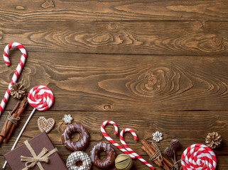 Christmas background with decorations and gift boxes on wooden background.  Christmas ornaments on wood with candy with copy space for your text.