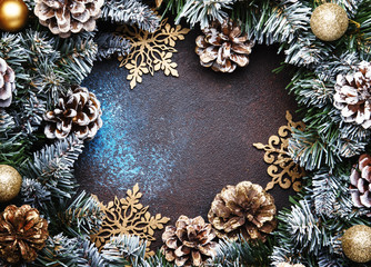 Christmas or New Year frame composition with  green snow fir branches, pine cones, golden snowflakes, Christmas balls on brown background, top view
