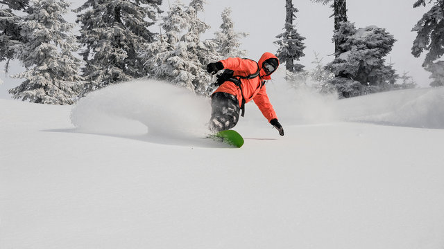 Man running down the mountain hill on the snowboard