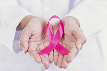 Woman holding pink ribbon. symbol of breast cancer awareness and international women day campaign.