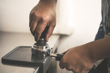 Barista using tamping for freshly roasted coffee bean make into a powder.