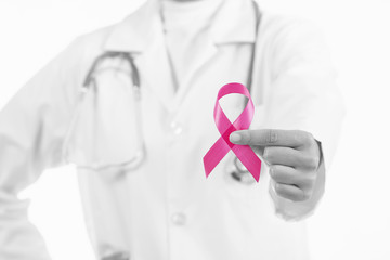 Doctor woman holding pink ribbon, supporting symbol of breast cancer awareness and international women day campaign.