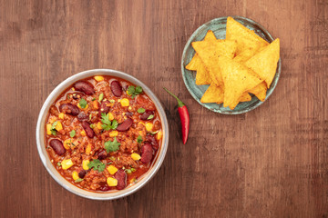 Chili con carne, traditional Mexican dish, shot from above with nacho chips, a chili pepper and copy space