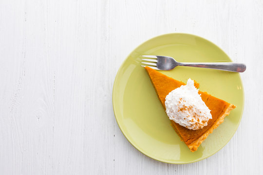 Slice of pumpkin pie with whipped cream over white wooden background