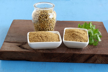 Coriander powder in two ceramic bowls and coriander leaves on a wooden table and seeds in a bottle.