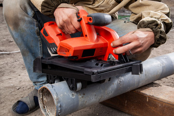 Close-up of a man  builder sawing metal  with a hand  modern  red circular saw at the construction site. Heavy industry worker cutting steel pipe with angle grinder in workshop.
