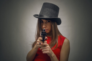 Dangerous woman in a bowler hat is aiming with her gun towards screen.