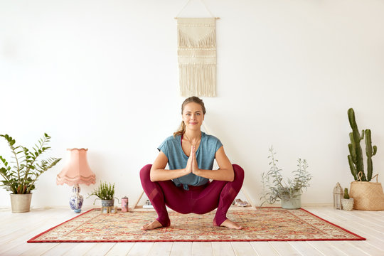 fitness, people and healthy lifestyle concept - young woman doing garland pose at yoga studio