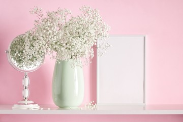 Blank mock up of photo frame on the pink background. Cosmetic table. Beautiful white flowers in a vase on a pink wall background, gift, mirror on a wooden shelf.