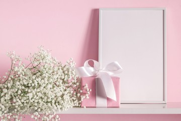 Blank mock up of photo frame on the pink background. Cosmetic table. Beautiful white flowers in a vase on a pink wall background, gift, on a wooden shelf.