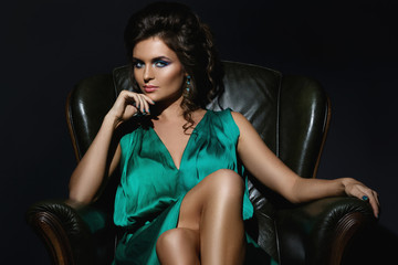Sexy woman in beautiful green dress posing on leather couch
