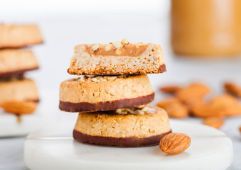 Homemade biscuit cookies with almond nuts and peanut butter on marble coasters on white kitchen table background.