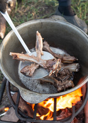 roasted meat in a cauldron on fire