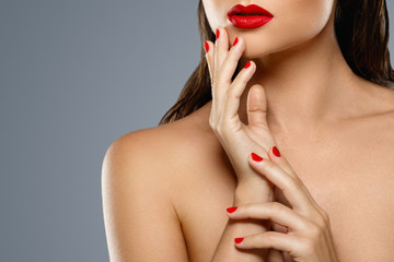 Beauty and cosmetics. Female mouth and nails with red manicure and lipstick.