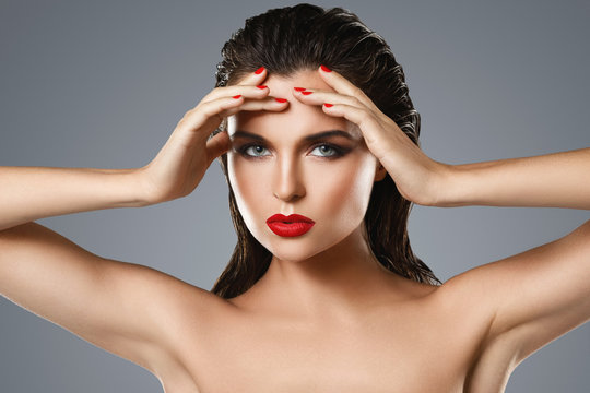 Portrait of beautiful young woman with a red lipstick and nail polish