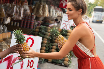 Young woman buying pineapples on the local Thai market