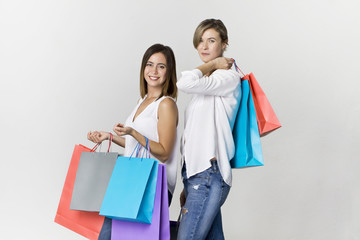Funny beautiful attractive relaxed carefree girls with shopping bags in white shirt and jeans isolated on white background