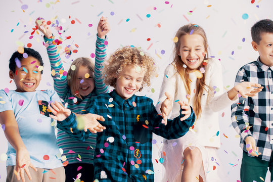 Smiling multicultural group of kids having fun with confetti during friend's birthday