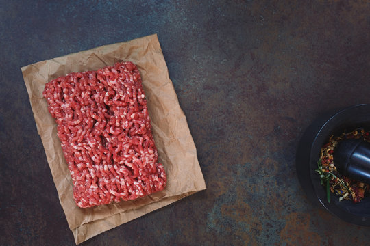Fresh raw grass fed angus ground beef on parchment paper, concrete rustic background, blank space, top view