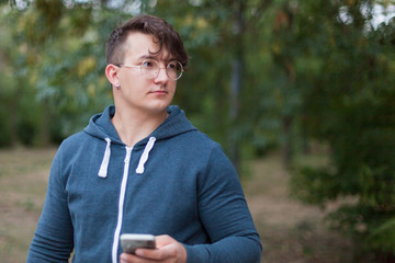 Attractive young caucasian man with dark curly hair, golden round glasses and earring holds the mobile phone standing in the park. Early autumn or summer. Outdoors, copy space. Diversity people