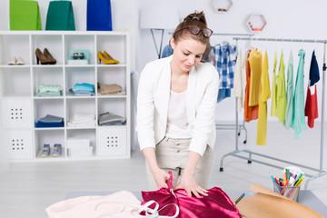 Creative fashion designer cutting fabric in an office