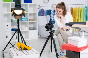 Businesswoman taking a photo of shoes in a studio