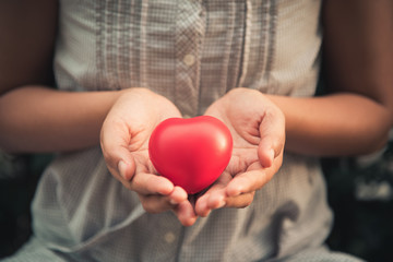 Woman hands holding red heart to giving someone