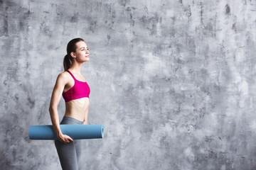 Woman standing holding yoga mat.