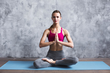 Beautiful woman in lotus position on yoga mat indoors.