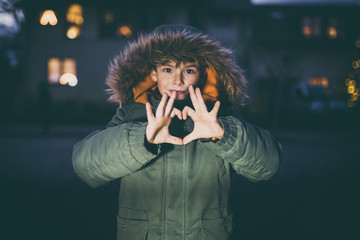 Boy showing love heart with hands outdoors with christmas lights